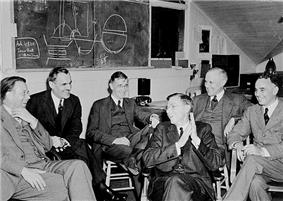 A group of in suits men sit around, laughing. On the blackboard behind is a discarded plan for assembling a uranium core.