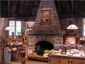 Interior photograph of the Leconte Memorial Lodge. Stone walls and several laden interpretive display tables surround a large stone fireplace with a bas-relief of Joseph LeConte.