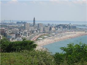 A distant view of a large city bordered by a beach.