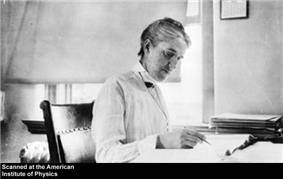 Woman sitting at desk writing, with short hair, long-sleeved white blouse and vest