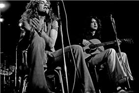 A black and white photograph of Robert Plant with a tambourine and Jimmy Page with an acoustic guitar seated and performing.