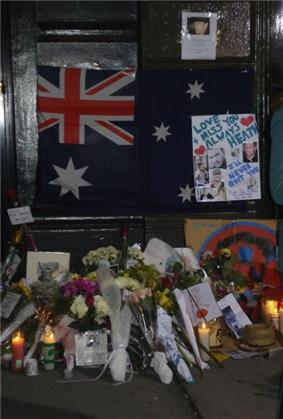 Dark doorway and doorstep with section of footpath. On the lower part of the dark door is a partly obscured Australian flag with dark blue background; red and white crosses on top left, large white star underneath and three white stars at the right with others obscured. Obscuring the right side of the flag is a white sheet with light blue writing,