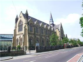 imposing neo-Gothic sandstone chapel, with modern buildings in the background