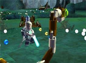 In a swamp-themed setting, a young man holds a futuristic sword-like weapon, apparently about to kill a large snake made of small plastic toy pieces. A short, somewhat cylindrical-shaped white and blue robot stands in the background. Visible in the foreground and background are many small disc-shaped objects; most of them are silver but some are gold or blue.