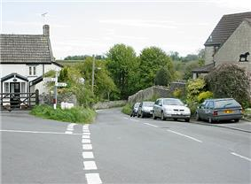 Street scene showing a road unction with parked cars. On the left and right are stone houses with trees and fields in the distance.