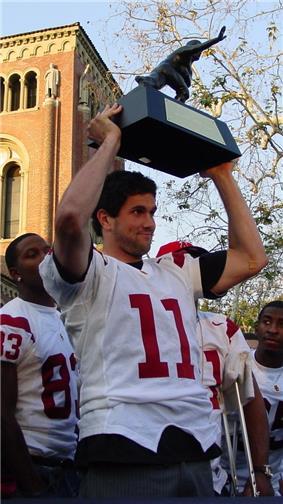 A picture of Matt Leinart holding his Heisman trophy.