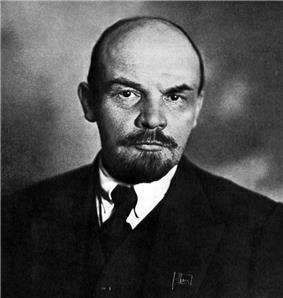 A bald man with a beard and a moustache, in a suit with a pale shirt and dark tie