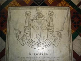 A white carved stone slab. At the top, a coat of arms with a shield of three cockerels, topped by a knight's helmet; underneath, the motto