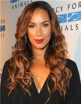 A woman with long, curly wearing looking directly forward, wearing a black outfit, and red lipstick.