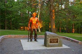 Life-size bronze statue of a shirtless man with a hat, resting his right hand on a pick axe and holding a shirt in his left hand. The top half of the statue is lit orange by the setting sun. A boulder to the right has a plaque that reads