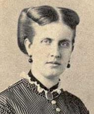 Half-length photographic portrait of a young lady with light-colored hair swept back and wearing a high-necked, dark Victorian era satin dress with dark buttons