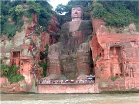 A giant seated buddha cut from a rock face.