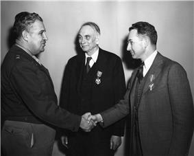 Two men in suits, with medals pinned on the left breast. One shakes hands with a fat man in an Army uniform.