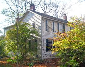 A white house with black shutters and brick chimneys seen from its front left corner. Shrubs and trees obscure the view on the sides.
