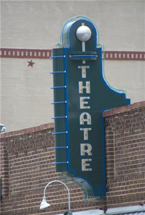 Photograph of an old theater sign on a rustic building.