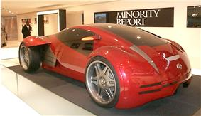 Futuristic two-door concept car displayed in front of a banner labeled