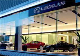 Car showroom with a coupe, two sedans, glass windows, plus large sign reading