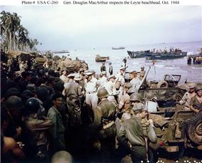 A large crowd of soldiers and jeeps on a beach. There are palm trees in the distance and landing craft offshore. A small group in the center conspicuously wear khaki uniforms and peaked caps instead of jungle green uniforms and helmets.