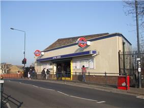 A white-bricked building with a dark blue, rectangular sign reading