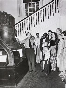 A man in uniform points to the Liberty Bell as a number of tourists, dressed in the fashions of sixty years ago, look on.