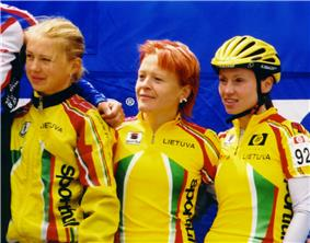 Three young women cyclists, standing in yellow team jerseys