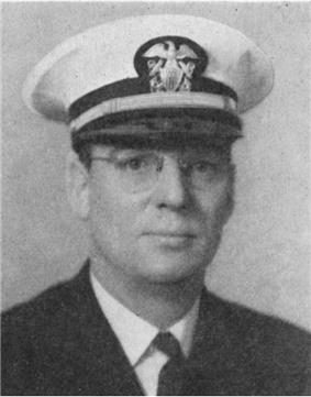 Head of a middle-aged white man wearing a white peaked cap, wire frame glasses, and a dark jacket over a shirt and tie.