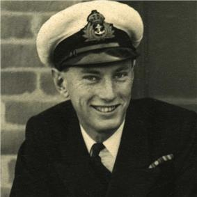 Monochrome photograph of head and shoulders of smiling young man (Lieutenant John Paul Wild RNVR) in white Royal Navy officer's cap and naval uniform.