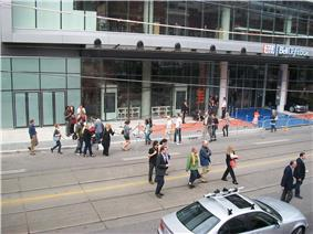 people milling around King Street in front of the TIFF Bell Lightbox, with rails and ropes set up around a carpets in front of the building