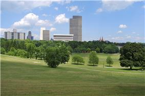 A green space with trees and rolling lawns is flanked by tall, modern-style buildings in the background on a sunny day.