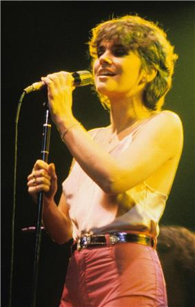 Ronstadt, in the summer of 1978, sings in concert dressed in a camisole top and pants with medium-length hair, clutching the microphone on a stand with both hands.