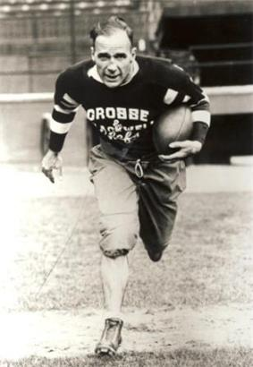 A football player in his mid thirties is seen running toward the camera with a ball tucked under his left arm.  He balding, and wearing a dark coloured uniform with the words