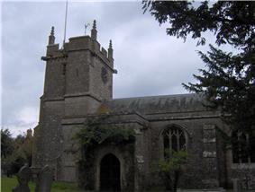 Stone building with square tower at left hand end. In the foreground are trees and gravestones.