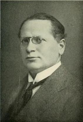 a picture of a middle-aged man with glasses wearing a suit and looking towards his left at the camera