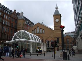 The end of a brick building with arched windows and sloping roofs lies between two towers with steeples. In front of this is a white metal and glass structure. People are standing and walking in the street in front.