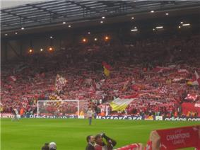 A single tiered stand that contains thousands of people. Several flags are being waved. In front of the stand is a grass pitch with a goal.