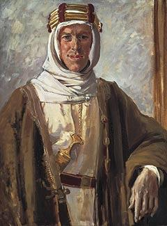 A man in white Bedouin-style robes and headdress, with a brown outer gown, from beneath which the handle of a sword or similar item protrudes
