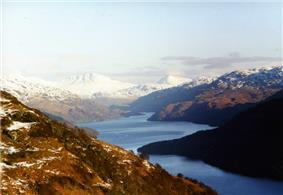 In the distance there are high snow-capped mountains, out of which a sinuous lake emerges. In the foreground lower brown hills surround the water.
