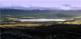 A relatively small loch on the River Spey is surrounded by forest and moorland. In the background can be seen the Cairngorm Mountains, the summits of which are covered with snow.
