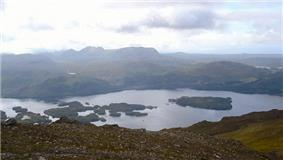 A view from above a lake containing several wooded islands with a wilderness of hills and moor beyond.
