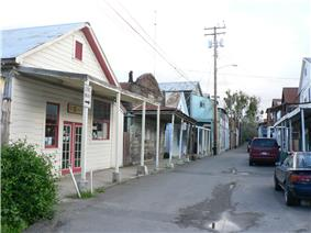 Photograph of a street in Locke, a narrow thoroughfare between tightly packed, single-story, wood-frame buildings.