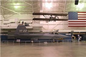 Starboard view of jet aircraft in museum among suspended aircraft and an American flag.