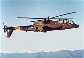 A side view of an AH-56 Cheyenne in hover, a few feet above a helipad.