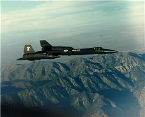 Sideview of black jet aircraft overflying mountain towards right of photo.