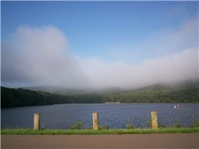 In the foreground a road with three wooden posts, a choppy blue lake behind with one small boat, ringed by green trees and low white clouds beneath a blue sky