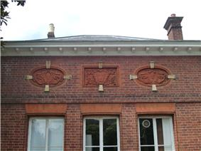colour photo of brick wall with three picture inlaid in the brick, a central shield bearing three fleur de lis flanked by two faces, all three elaborately framed. Also windows below and roof above.