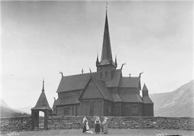 A timber framed, wooden church with  plank walls and tiered roof, steeply pitched. It has a tall, slender spire and few windows.