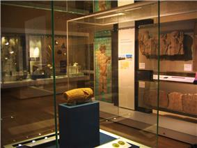 View of the Cyrus Cylinder in its display cabinet, situated behind glass on a display stand. Other ancient Persian artifacts can be seen lining the room in the background.