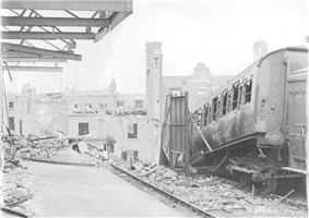 A railway platform strewn with rubble. Broken girders jut out above the platform, while alongside the platform a set of railway lines stop abruptly at a large crater. Next to the railway line is a burned-out railway carriage tilted at an acute angle.
