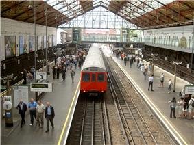 The interior of a building with windows on the ceiling and a railway track running from the background to the foreground in the centre