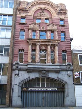 Narrow four storey red building above a wide archway